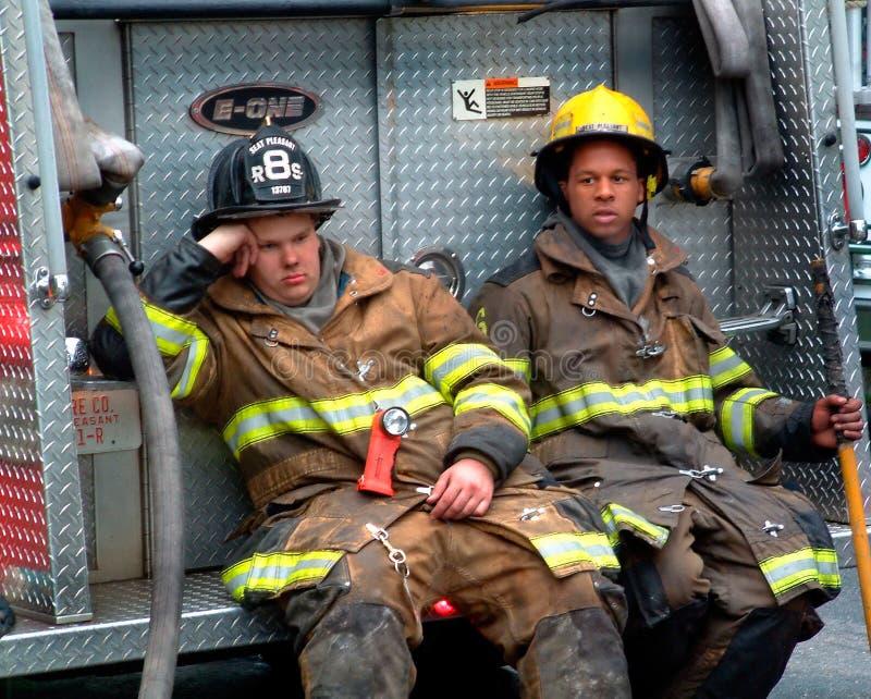 Deux sapeurs-pompiers prenant une lutte contre l'incendie d'ifrom de coupure à un feu t de maison photo stock