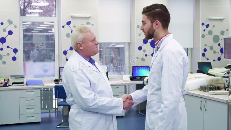 Deux scientifiques masculins se saluent au laboratoire images stock