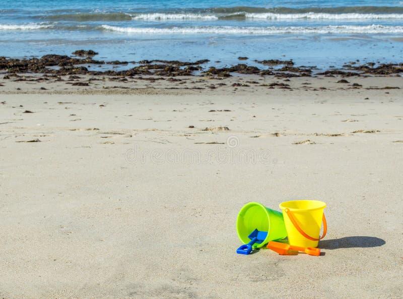 Deux seaux en plastique de sable avec des pelles sur une plage sablonneuse photos libres de droits