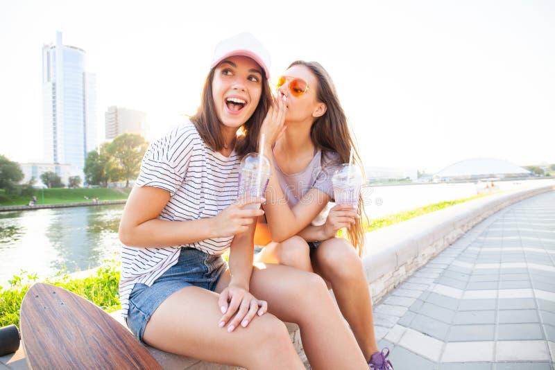 Deux secrets assez plus mignons d'actions d'adolescents, bavardage Étonnez le visage, émotions, meilleurs amis utilisant l'équipe images stock