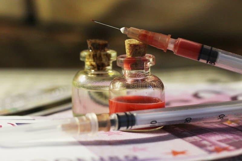 Deux seringues, médecines et argents médicaux si étroits photo libre de droits