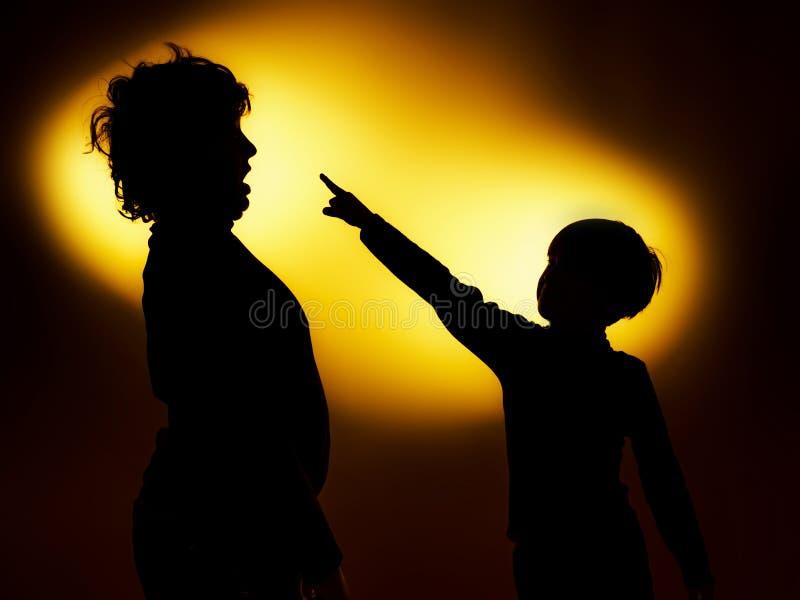 Deux silhouettes du garçon expressif montrant des émotions utilisant le gesticu photos stock