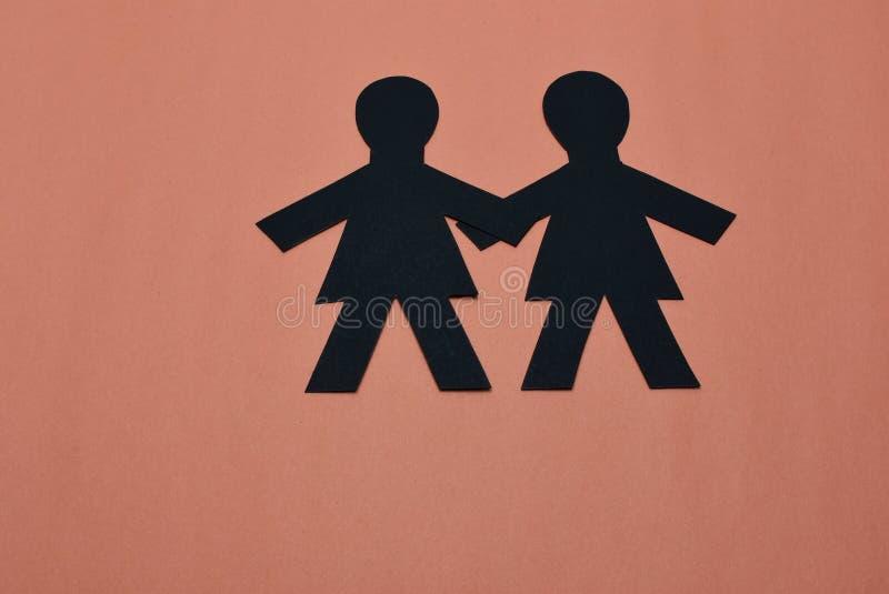 Deux silhouettes femelles dans le noir avec le fond orange image libre de droits