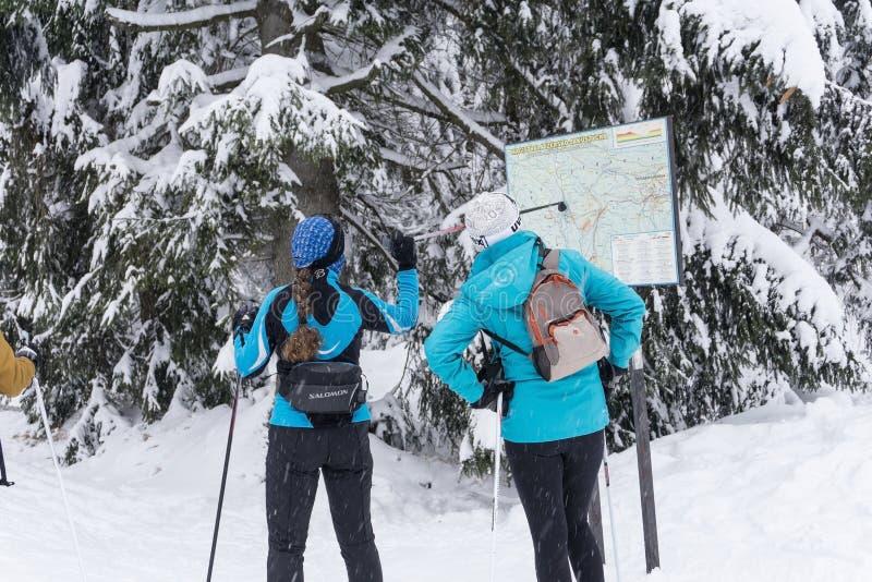 Deux skieurs féminins recherchant un itinéraire transnational sur la carte photographie stock