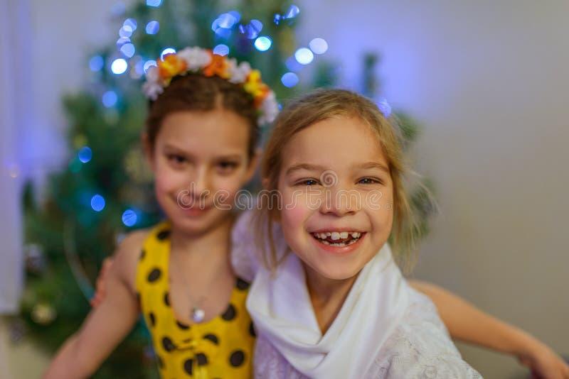 Deux soeurs autour d'arbre de Noël photos stock