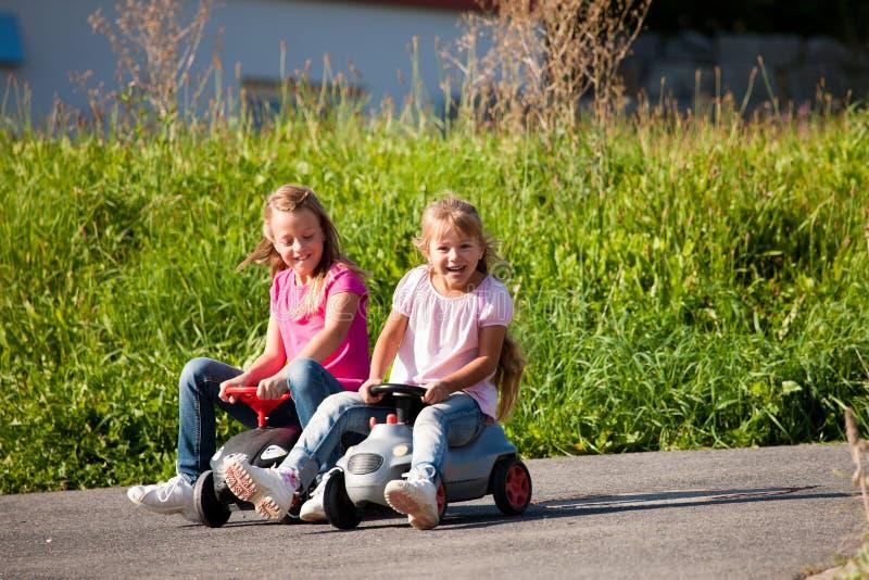 Deux soeurs avec des véhicules de jouet image stock