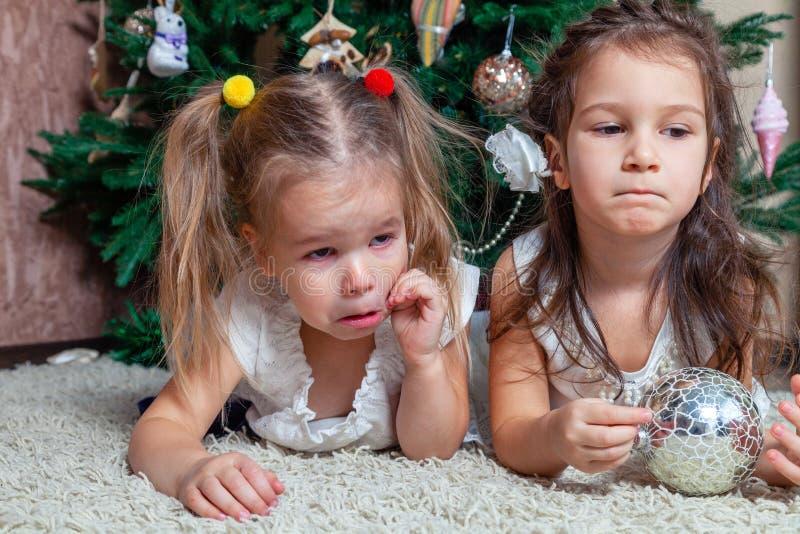 Deux soeurs bouleversées se trouvant sous l'arbre de vacances On a pris le Chr images stock