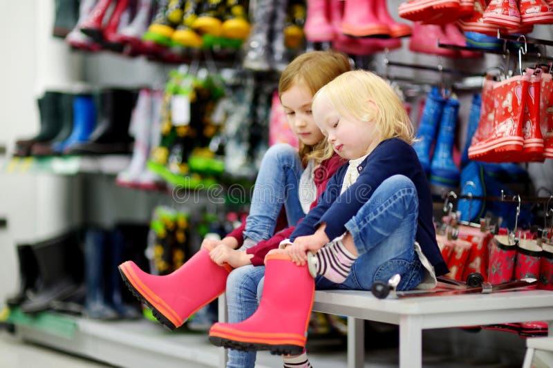 Deux soeurs choisissant et essayant sur de nouvelles bottes de pluie photos libres de droits