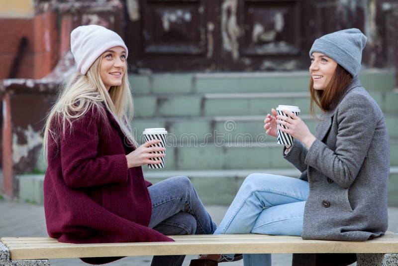 Deux soeurs détendant et buvant du café Croissant doux et une cuvette de café à l'arrière-plan le café vont à Le portrait de mode photographie stock