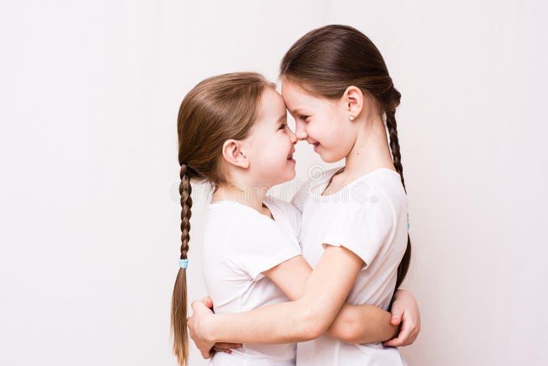 Deux soeurs de filles s'étreignent doucement en se réunissant photos stock