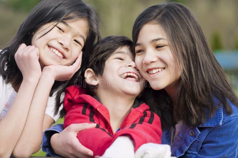 Deux soeurs et leur petit frère handicapé photo libre de droits