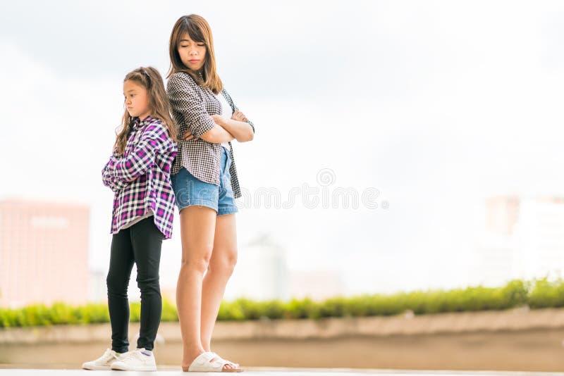 Deux soeurs folles à l'un l'autre, à la question de famille ou au concept de relations, avec l'espace de copie photo stock