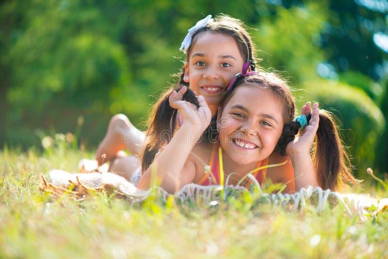 Deux soeurs heureuses ayant l'amusement dans le parc image libre de droits