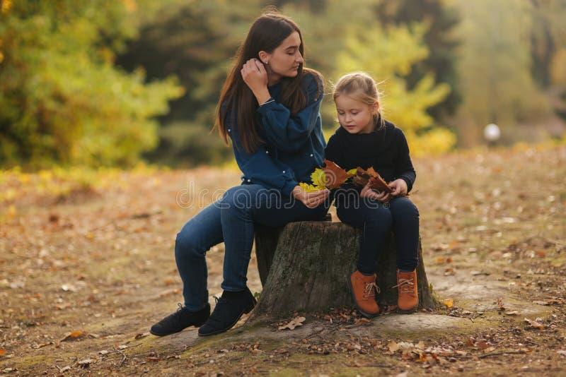 Deux soeurs heureuses marchant en parc pendant l'automne Peu soeur avec la soeur adolescente photo stock
