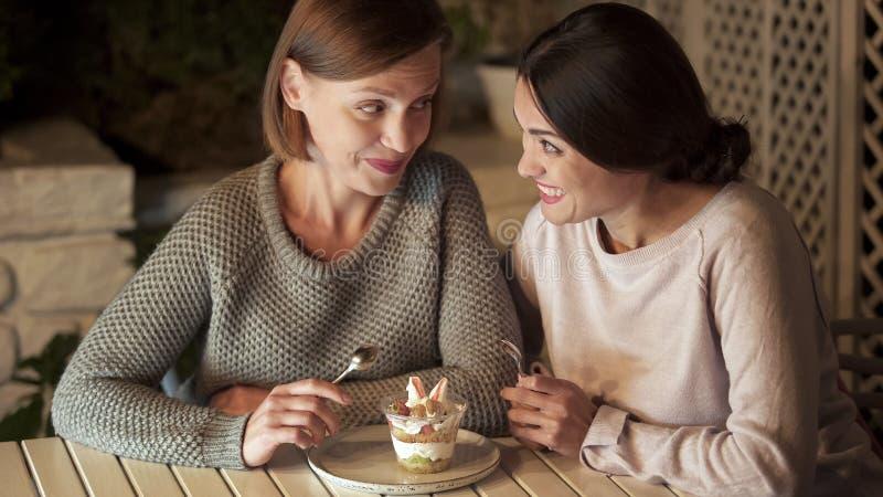 Deux soeurs heureuses tenant des cuillères, préparant mangent le dessert crémeux doux, loisirs images libres de droits