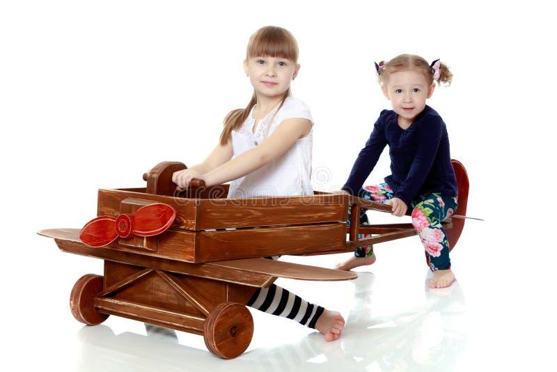 Deux soeurs jouant dans un avion en bois photos stock