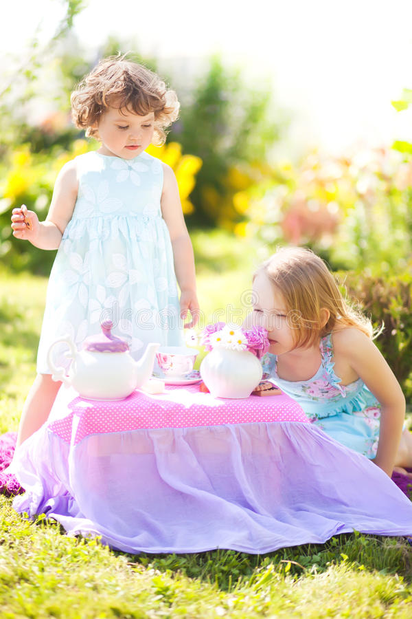 Deux soeurs jouant le thé dehors photos stock