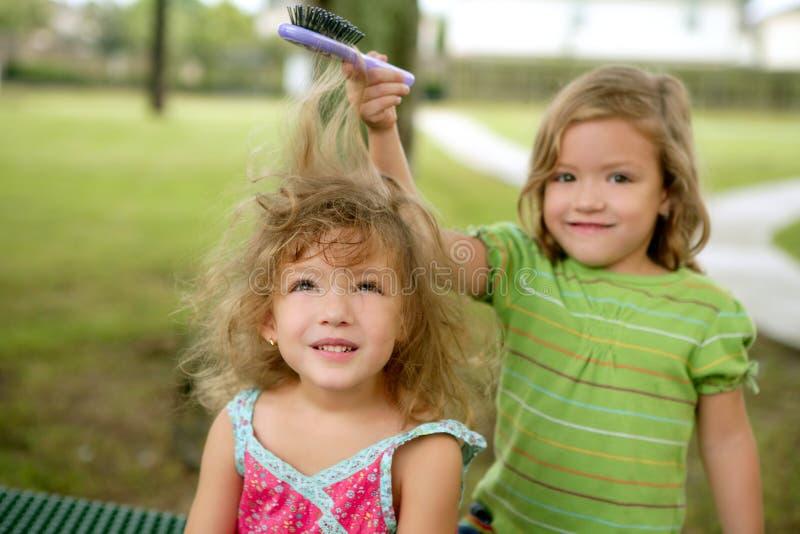 Deux soeurs jumelles feignant pour être coiffeur photo stock