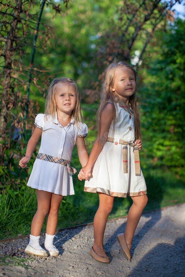 Deux soeurs mignonnes de mode entrent main dans la main dans photographie stock libre de droits