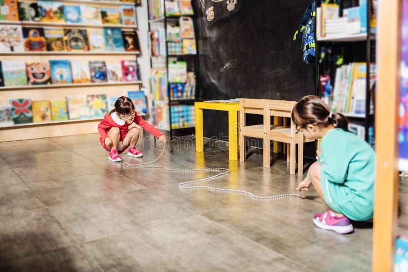 Deux soeurs portant les mêmes robes lumineuses ayant l'amusement dans la bibliothèque d'enfants images libres de droits