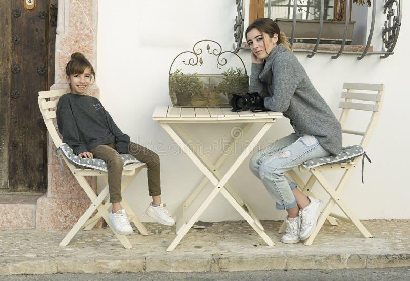 Deux soeurs s'asseyant à la porte d'un hôtel image stock