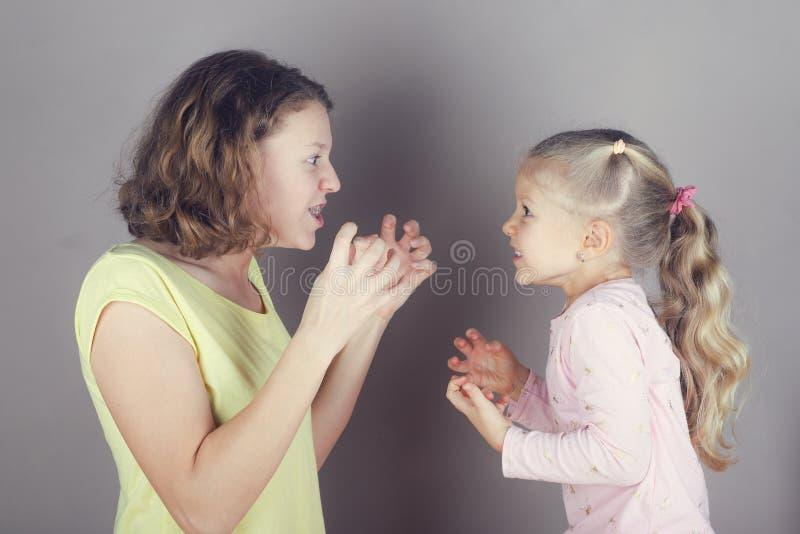 Deux soeurs se disputent, discutent et ondulent leurs bras photographie stock