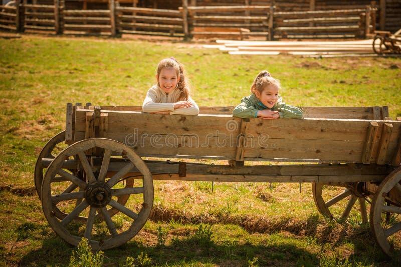 Deux soeurs sur le vieux chariot en bois photographie stock