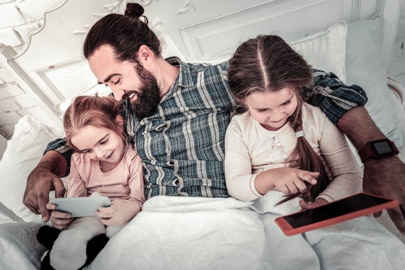 Deux soeurs toujours dans le lit jouant des jeux au téléphone avec leur papa dans le lit images libres de droits