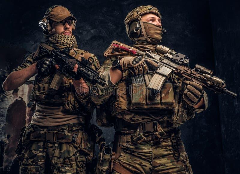 Deux soldats de forces spéciales dans le plein équipement de protection avec des fusils d'assaut r photo stock