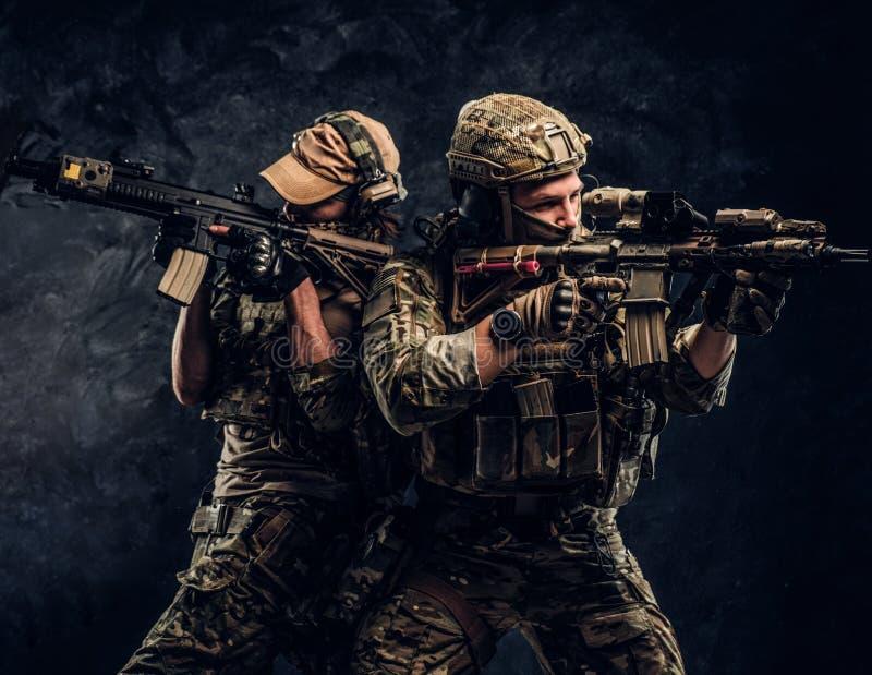 Deux soldats de forces spéciales dans de pleins fusils d'assaut et viser de participation d'équipement de protection les cibles P photographie stock