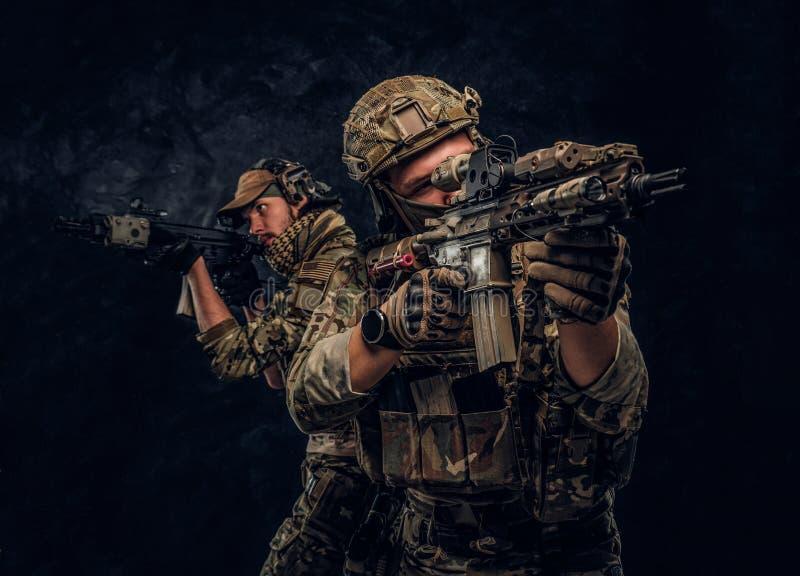 Deux soldats de forces sp?ciales dans de pleins fusils d'assaut et viser de participation d'?quipement de protection les cibles P image libre de droits