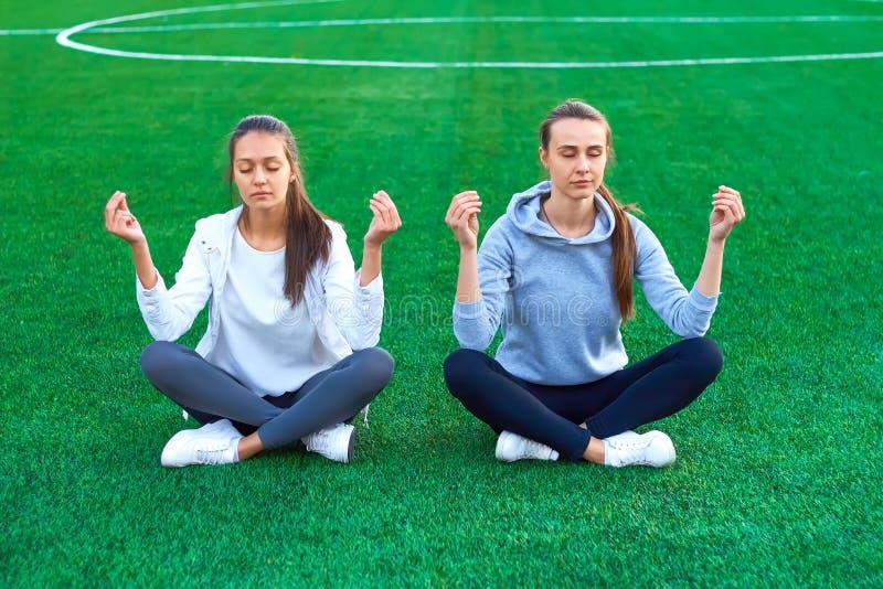 Deux sports de fille faisant étirant la forme physique s'exerce en parc de ville sur l'herbe verte Yoga en nature Matin photos libres de droits