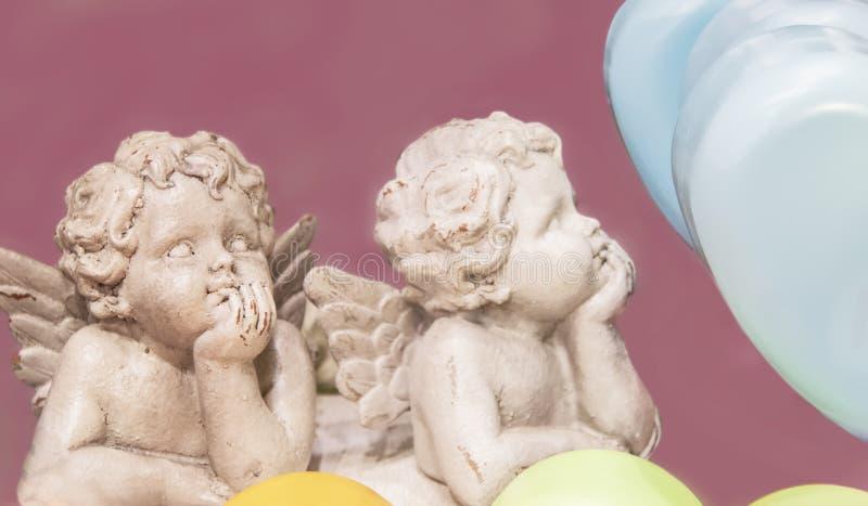 Deux statues ébréchées d'ange avec des mentons sur des mains entourées par les coeurs en pastel d'isolement sur le fond rose pour image stock