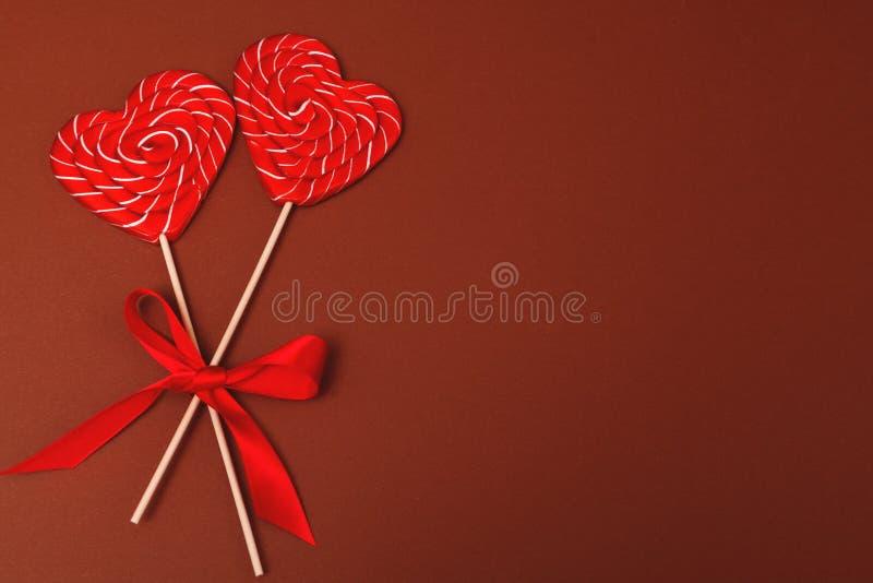 Deux sucreries en forme de coeur Lucettes de Saint-Valentin sur le fond brun Fond de Saint-Valentin, jour du mariage image stock