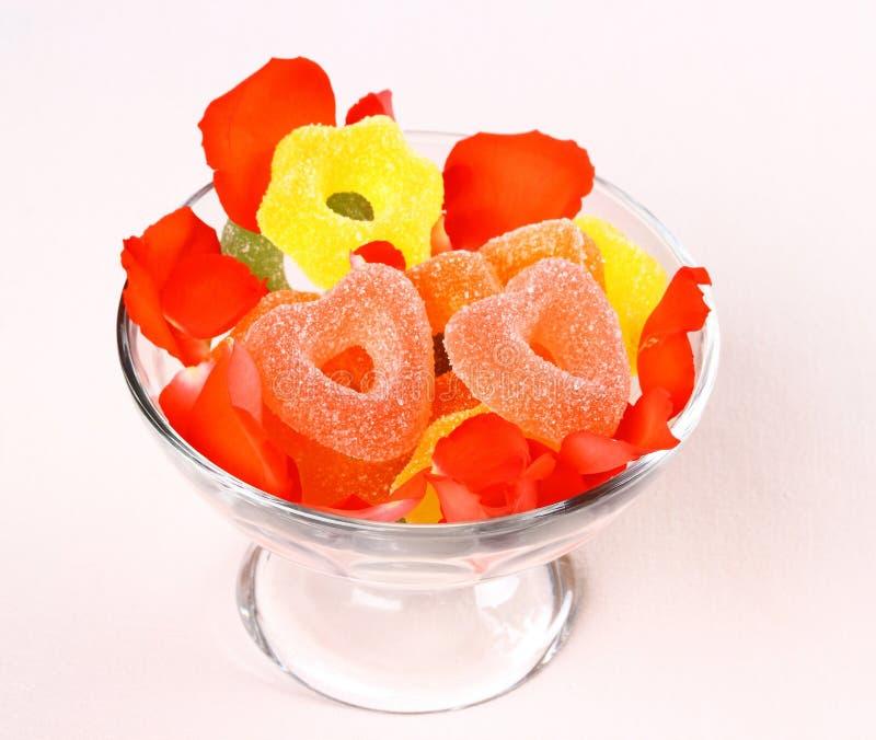 Deux sucreries rouges de coeurs dans le bol en verre et des pétales de rose photo libre de droits