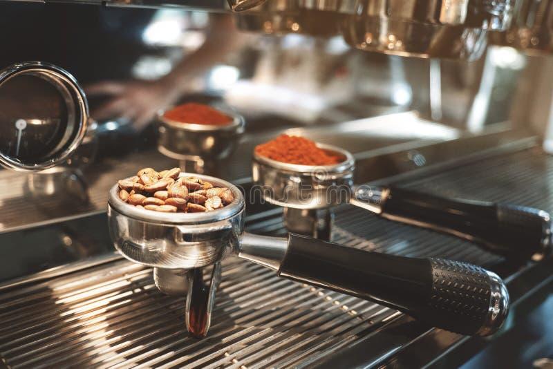 Deux supports un de café avec le cafè moulu frais un autre avec les haricots rôtis se tenant sur la machine professionnelle de ca photo stock
