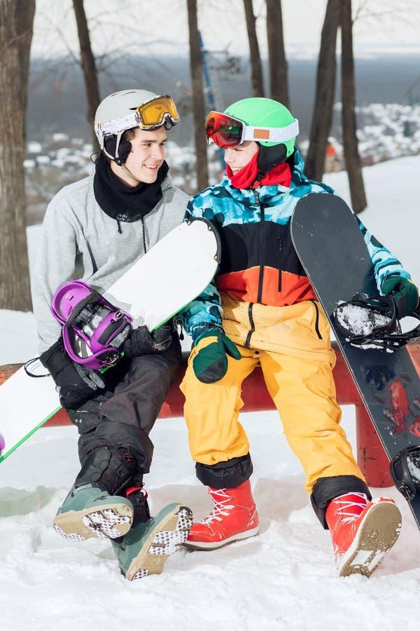 Deux surfeurs amoureux aimants se reposant sur le dessus de la pente de ski photographie stock