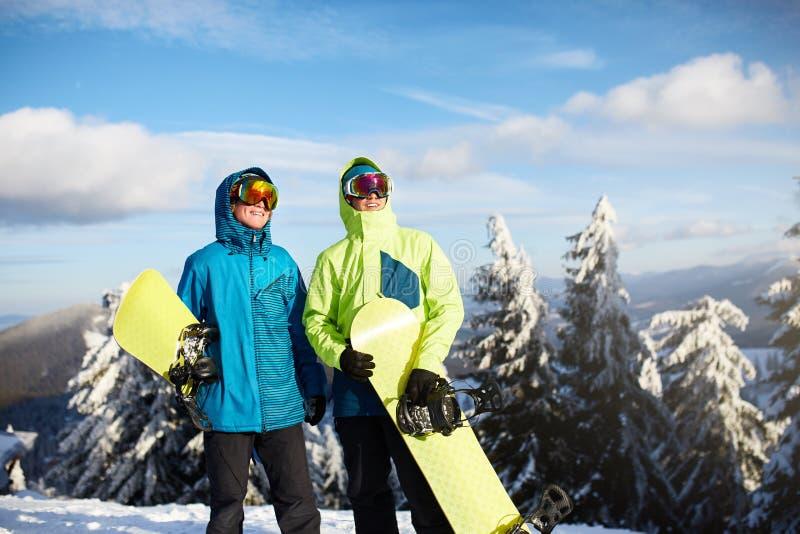 Deux surfeurs posant à la station de sports d'hiver Amis de cavaliers portant leurs surfs des neiges par la forêt pour le freerid image stock