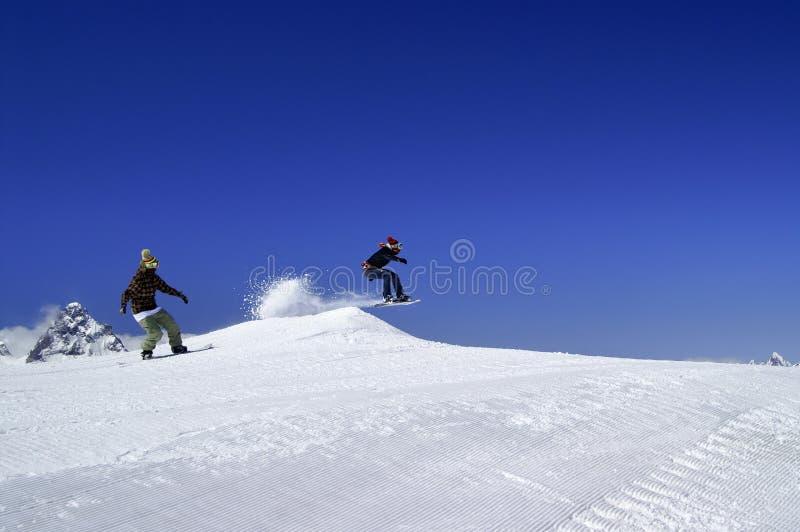 Deux surfeurs sautent en parc de neige à la station de sports d'hiver l'hiver ensoleillé photo stock