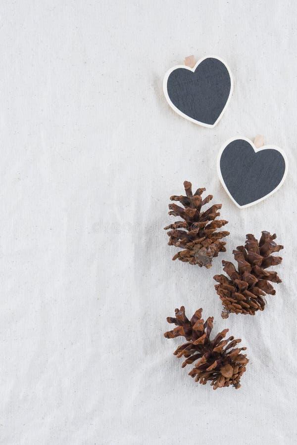Deux tableaux noirs minuscules de forme de coeur avec des pinecones photographie stock libre de droits