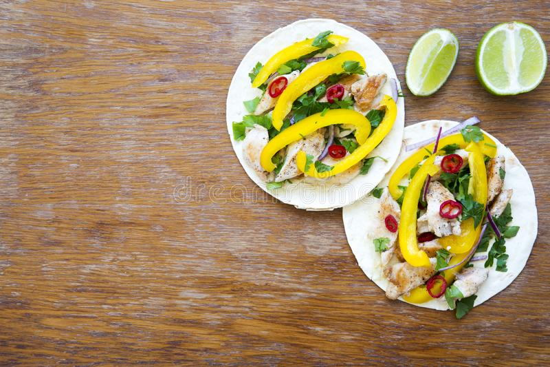 Deux tacos avec le filet grillé de poulet, légumes frais, chaux dessus photos stock