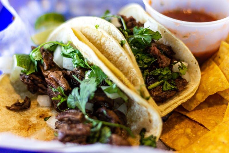 Deux tacos d'asada de carne avec le cilatro et oignon sur des tortillas de ma?s photos stock