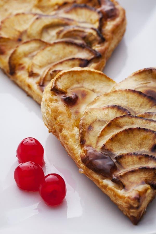 Deux tartes aux pommes de Saint-Valentin et trois cerises glacées photo libre de droits