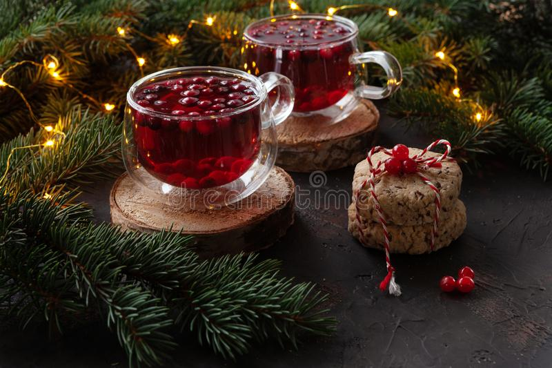 Deux tasses avec la boisson épicée de Noël chaud avec la canneberge et les gâteaux photo stock
