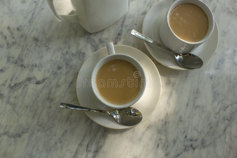 Deux tasses avec la boisson au lait des plats avec des cuillères près de la théière en céramique sur la vue supérieure en gros pl image stock