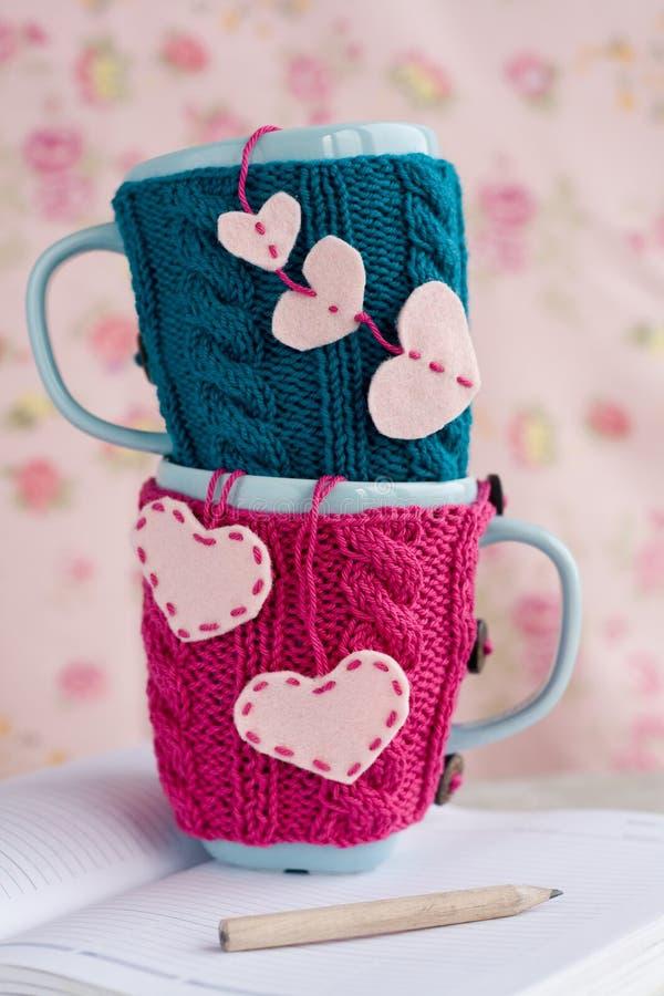 Deux tasses bleues dans le chandail bleu et rose avec des coeurs de feutre sur un carnet photo libre de droits
