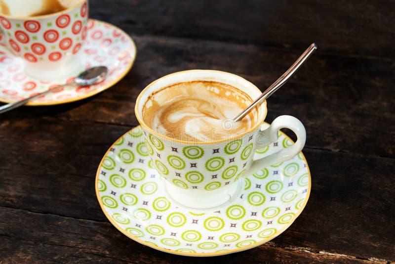 Deux tasses colorées avec le cappuccino chaud sur une table en bois image libre de droits