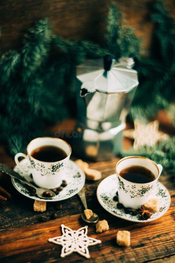 Deux tasses d'expresso avec des morceaux de sucre de canne et de fabricant de café italien sur la table en bois photos libres de droits