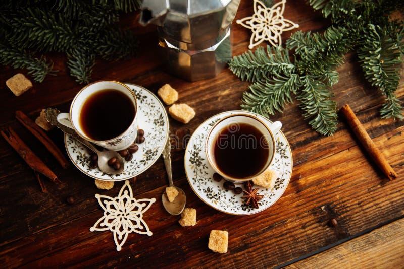 Deux tasses d'expresso avec des morceaux de sucre de canne et de fabricant de café italien sur la table en bois photos stock