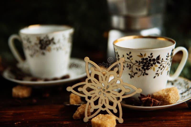 Deux tasses d'expresso avec des morceaux de sucre de canne et de fabricant de café italien sur la table en bois photographie stock libre de droits